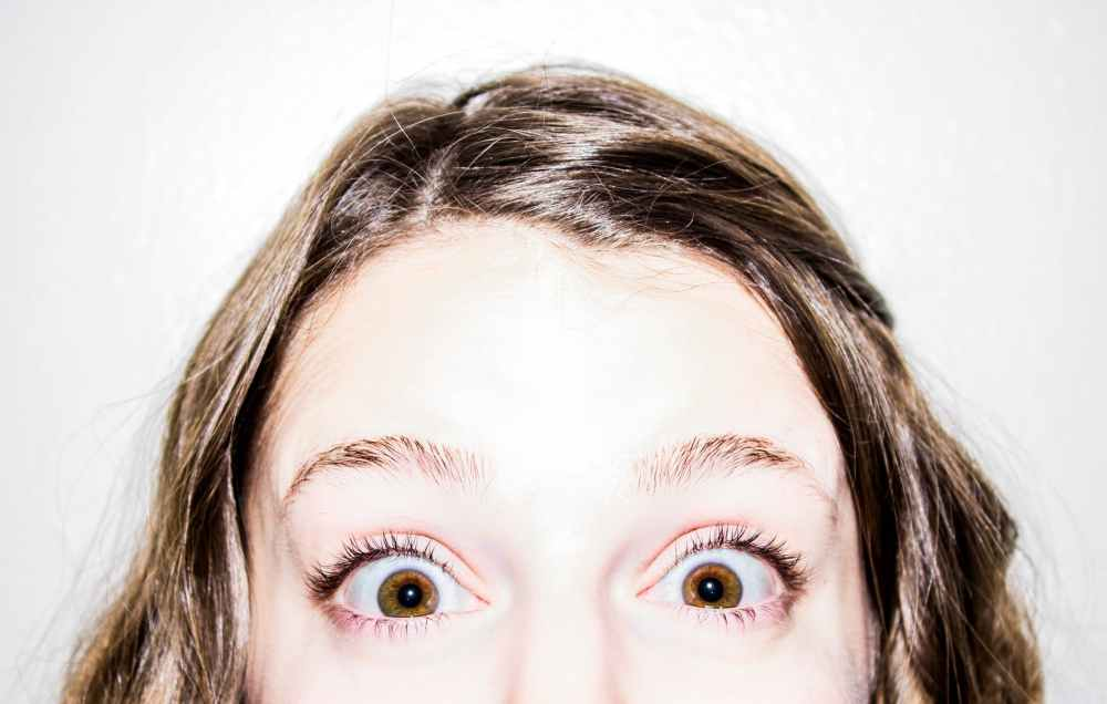 Girl with a shocked look on her face and brown hair. Photo by pexels.com
