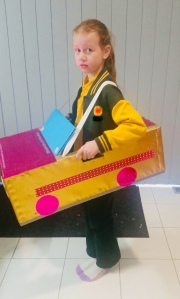 Mia wearing a car constructed from a painted cardboard box (facing side on)