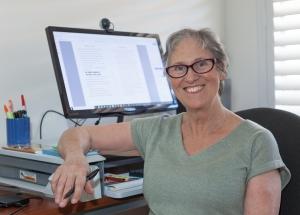 Photo of Teena Raffa-Mulligan in a grey shirt sitting at her computer desk.