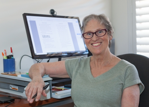 Photo of Teena Raffa-Mulligan in a grey shirt sitting at her computer desk.
