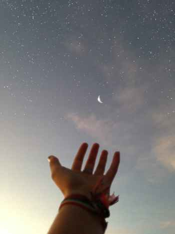 A hand with palm up towards a crescent moon and stars in a pale evening sky. Photo courtesy of pexels.com
