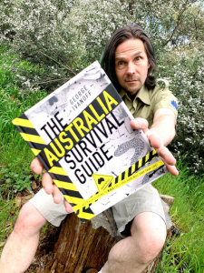 George Ivanoff holding a copy of The Australia Survival Guide