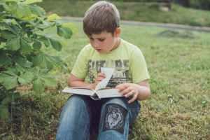 Boy reading. Photo by Tanya Gorelova via pexels.com.