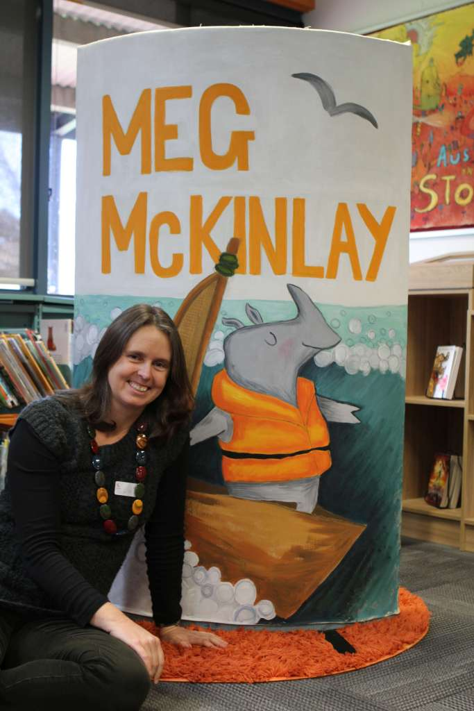 Meg McKinlay, author, sitting in a library